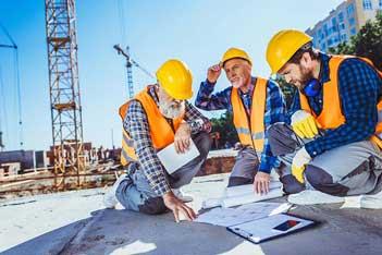 Workmen looking over blueprints